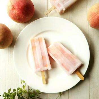 白桃とグラニュー糖、レモン汁で作る桃のコンポート。さらにそのコンポートに練乳、シロップを加えて作る、ほんのりピンク色の見た目も素敵なアイスキャンディー。桃のコンポートのレシピも載っているので2つのデザートを作ることができる、美味しくお得なレシピです。