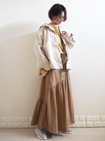 イエローのトップスにロングスカートを合わせたスタイリング。切り返しのロングスカートをセレクトすると、立体感のあるスタイリングに。ホワイトのミリタリージャケットを羽織れば、マニッシュで落ち着きのあるコーディネートになります。