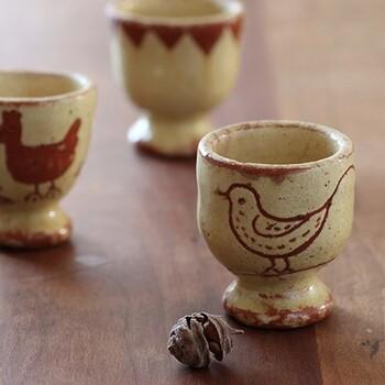1900年代初頭のスウェーデンで作られたという、貴重なヴィンテージのエッグカップ。素朴な風合いの陶器に、小鳥、ニワトリ、ヒヨコの行列など愛らしい絵が1点1点描かれています。