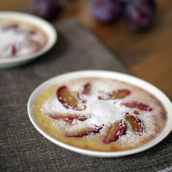 お皿の上に花が咲いたようなプラムのフルーツグラタン。カットしたプラムを並べ、カスタードプリンのような生地を流し込んでこんがり焼くだけ。仕上げに粉糖をまぶしたら完成です。