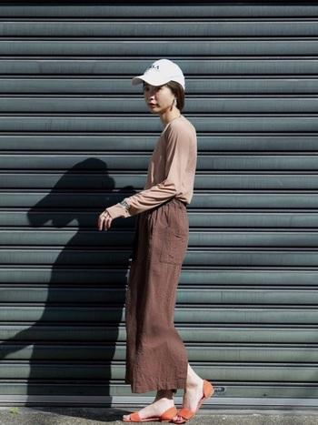 ブラウンのタイトスカートにサンダル。フェミニンなスタイルにキャップを合わせて、ぬけ感をうまく演出しています。