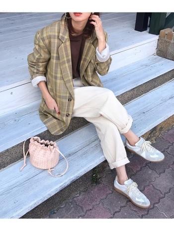 70年代には、女性があえて男性サイズのジャケットを着ることが流行りました。大きめのジャケットを着ることで、逆に華奢な女性らしさが強調される、今にも通じるコーデテクニックです。 今っぽくカジュアルダウンさせるなら、インナーをTシャツにしたり、スニーカーを合わせたりするのがおすすめ。