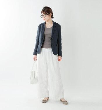 ベーシックなリネン素材のテーラードジャケットは、夏のビジネススタイルにおすすめ。通気性がいいので長時間着ても着心地が◎ ネイビーのジャケットを白のワイドパンツと合わせて涼しげに。