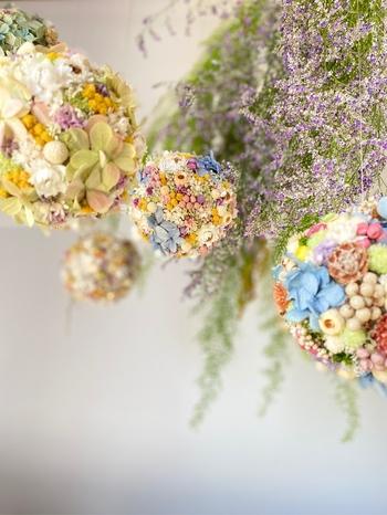 ドライフラワーやプリザーブドフラワーの色とりどりの小花や実をぎゅっと詰め込んだ、お花畑のようなフラワーボール。カラーによっても雰囲気が異なるので、紐の長さを調節していくつか飾っても◎