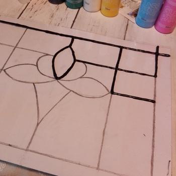 紙にガラスシートを乗せて固定します。先ほど書いた下絵通りに黒のガラス絵の具を使って縁取っていきます。