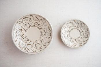 300年続く沖縄にある窯元、育陶園で作られている唐草模様のやちむん。やちむんといえば大胆でおおらかな染付が特徴ですが、こちらのやちむんは繊細な彫模様が施されており、従来のやちむんにはない美しさを持ったお皿です。