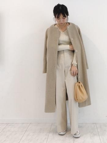 薄ベージュのワイドパンツに、同系色のトップスとコートを合わせたワントーンコーデ。手に持った巾着バッグはトーン違いのベージュをチョイスして、さりげないアクセントに。足元をあえてスニーカーにすることで、フェミニンな着こなしを程よくカジュアルダウンしています。