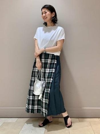 首元の詰まった白Tは、黒いチェックのスカートで大人カジュアルな着こなしに。バッグをシルバーにすれば涼しさとトレンド感をプラスできますよ。