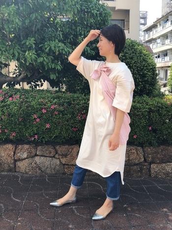 白のTシャツワンピにデニムパンツを合わせた、夏の定番コーディネート。ピンクのシャツを羽織らずにあえてたすき掛けのように巻くことで、ほどよいワンアクセントをプラスしたコーディネートです。もちろん肌寒さを感じればすぐに羽織ることもできるので、初夏にぴったりの着こなしですね♪