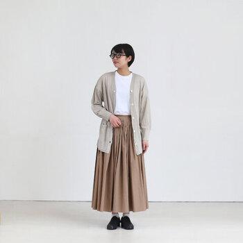 ベージュのロングスカートに、トーン違いのベージュカーディガンを合わせたコーディネートです。トップスは白でとことんナチュラルな印象に。暖色系のアイテムで全体が膨らんで見えないよう、足元を黒シューズで引き締めているのもポイントです。
