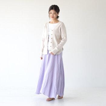 パープルのロングスカートに、白トップスを合わせたベーシックなコーディネート。上から白のカーディガンを羽織ると、女性らしさがグッと高まります。同色のトップスとカーディガンを合わせる際は、素材違いを意識すればぼんやりとした印象になりません。