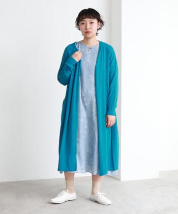 薄いブルーの総柄ワンピースに、ターコイズブルーのロングカーディガンを合わせたコーディネートです。同系色で揃えれば、セットアップ感覚で着用できます。足元はベージュの靴下と白のシューズでとことん爽やかな印象に。ブルーを主役に据えている着こなしなので、小物類は白やベージュで色を揃えるのがおすすめです。