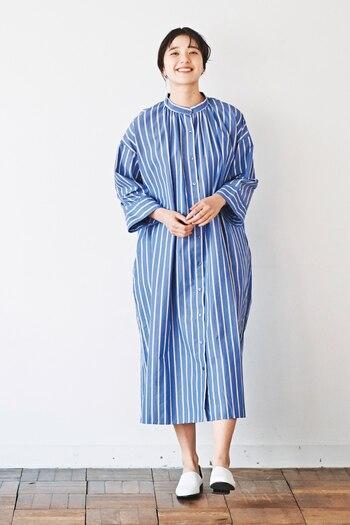 青と白のストライプが、爽やかな印象を与えるシャツワンピース。オーバーシルエットとスタンドカラーが特徴で、一枚でもサラッと着こなせるようなデザインに仕上げています。袖丈は長めですが、ボタンなしの袖なので気温に合わせてロールアップすれば程よい抜け感もプラスできます。