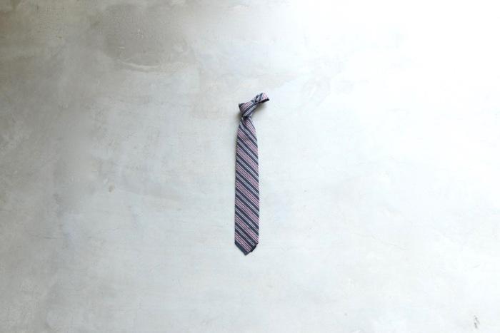 シンプルなストライプ柄のネクタイはEngineered Garments(エンジニアードガーメンツ)のもの。よく見るとシアサッカー地なのが季節感もありおしゃれ。これからの装いにおすすめのネクタイです。