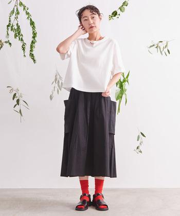 すこし丈の短い白Tは、ウエストが高めのスカートを合わせてスタイルアップ。赤いソックスとサンダルで足元にアクセントを作ればらしさが詰まった着こなしに。
