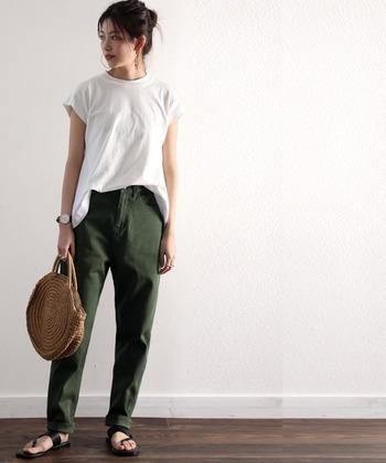 短めの袖がお洒落な白Tに、カーキのテーパードパンツを合わせ、程よくカジュアルに。サンダルやかごバッグで軽さを出して。