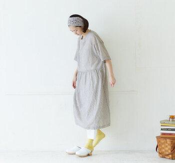透け感のあるリネン素材のストライプ柄のワンピースを主役に。夏にぴったりなシンプルなワンピースに、ヘアバンドとカラーの靴下がアクセントになっています。インナーのパンツとサンダルのカラーの白が、コーディネート全体をさわやかな雰囲気に。体のラインをひろわないワンピースは、リラックスしたいシーンにおすすめです。