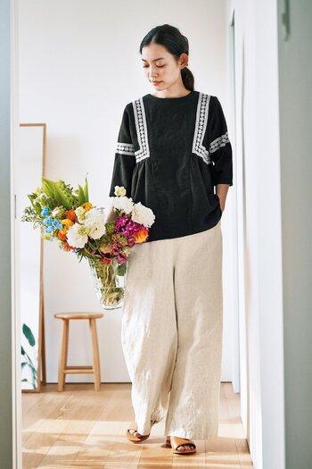 リラックスシーンにはリネン素材のワイドパンツがおすすめです。民族衣装のようなデザインのトップスと相性抜群で、リッチなリゾート感に!