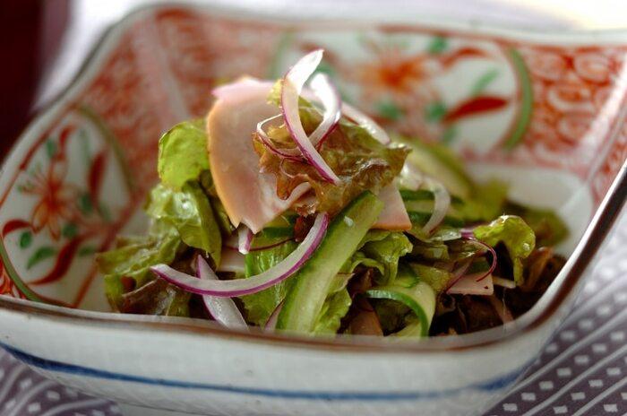 レタス、きゅうり、ハムを使った定番サラダ。オリーブオイルに塩こしょうとレモン汁を加えたシンプルなドレッシングで和えてさっぱりと。オムライスのワンプレートに一緒に盛り付けるのもいいですね。