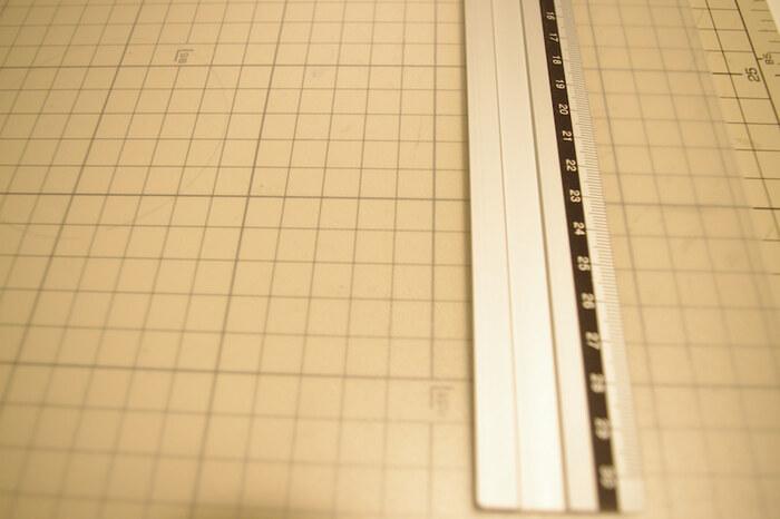 定規をあてて、カッターで浅く切り込みを入れます。この時、完全にカットしてしまわないように注意しましょう。切り込みに沿って折り曲げると、綺麗に折り目をつけることができます。