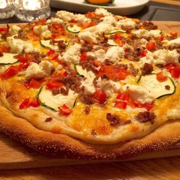 市販のピザ生地に、リコッタチーズとひき肉、野菜を散らすようにトッピングしています。リコッタチーズにすることで、あっさり食べられます。ズッキーニ、トマト、パプリカなど、カラフルな野菜を使うのがポイント。