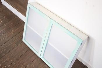 爽やかなブルーの木枠の収納棚。扉部分にPPシートを貼っています。洗面所の壁に取り付ければ、ごちゃごちゃしがちな洗面用具をすっきりと収納できます。