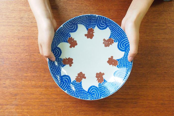 にわとりが器の縁をぐるりと囲んだユニークなデザインのプレート。印判手という技法で一枚ずつ丁寧に作られた、レトロで遊び心を感じる和食器です。
