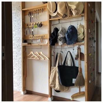 玄関に作ったディアウォールの収納ラック。右側は棚にラックを付けて、帽子やバッグをかけています。左側は、縦にした棚板にフックを付けて、時計や鍵をかけるというナイスアイデア!外出時に必要なものを掛けておけば、忘れ物もなくなりそう。