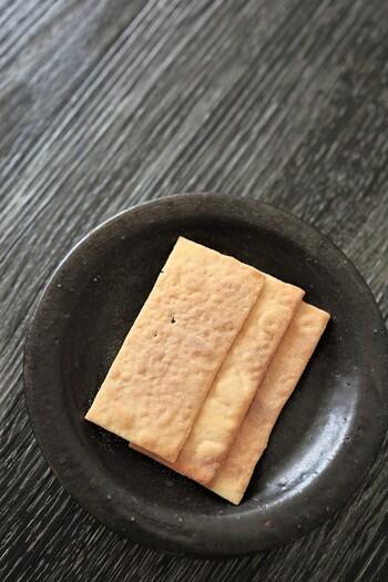 この銘菓を考案したのは、四代目当主。今から遡ること約250年程前の安永年間です。  儚いほどに薄い菓子は、蕎麦粉の生地を薄く伸ばして、丁寧に焼き上げたもの。すべて手作業で作るため、一枚一枚微妙に形が異なって、それがまた上品な風情を醸し出しています。薄くてもパリッとしっかりとした食感ですが、軽やか。蕎麦の香りと甘みが口中でたゆたうような、滋味で風雅な味わいです。  【『竹流し』は、尾太鉱山の竹を鋳型にして固めた金の延べ板に、四代目が着想を得て、地元の蕎麦を材料に作られたと伝わる。北東北は鉱脈が多く、江戸期から銀、銅を産して津軽藩を潤わせていた。白神山地東部の尾太鉱山はその最たるもので、日本有数の金属鉱山の一つ。】