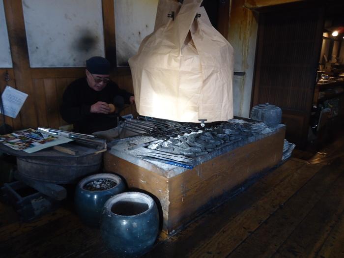 「八重吉煎餅店」の創業は、昭和9(1934)年。「大浪」で修行した創業者が、一関北方の江刺に店を構え、以来地元で愛されてきた煎餅の老舗です。創業者の先代が磨いた技と味は、現在の二代目店主へと引き継がれ、今も昔ながらに、手間を惜しまず、一枚一枚炭火で亀の子せんべいを手焼きしています。  【『亀の子煎餅』は、完成まで二日間がかり。まずは、丸い焼き型に小麦粉と砂糖と水で作った生地を流し込み、弱火でじっくりとに焼き上げる。焼けた煎餅を型から外したら、せんべいが熱い内に端をつまんで亀甲型に仕立てる。整形後、黒胡麻蜜をかけ、炭火の上の籠の中に入れ、一晩寝かせ、翌日、煎餅を焼く炭火の熱で燻すようにして、黒胡麻蜜をじっくりと乾かし、ようやく完成する。  画像は、「八重吉煎餅店」の煎餅焼き場に座る二代目店主。一枚一枚、焼き型を用いて炭火で丁寧に焼いている。上部の紙に覆われているのが、前日仕込んだ黒胡麻蜜かけの煎餅が入った籠。紙の下部分は開いていて、炭火の熱が籠に入るようになっている。】