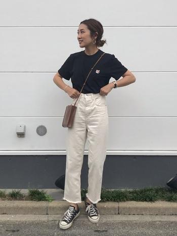 ワンポイントイラストが入ったTシャツは、ブラックカラーをチョイスすることで大人っぽく。ホワイトのデニムでモノトーンにまとめたら、ベルトの細いポシェットで絶妙な抜け感をプラス。