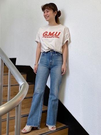 胸に大きめのロゴの入ったTシャツはコーディネート全体をグッとカジュアルなムードに導いてくれます。幼くなってしまわぬよう、デニムはフレアの効いたシルエットを、足元にはオープントゥのヒールを合わせるとレディな雰囲気がプラスされます。