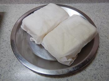 絹ごし豆腐を厚手のキッチンペーパーで包んで、片手で少しずつ力を加えながら水切りしましょう。絹ごし豆腐のなめらかさを生かしながら、余分な水分を取り除けます。力加減が不安な人は、このまま500Wで2~3分レンチンしましょう。  さらに水分を落としたい人は、お皿をのせてしばらく置くともっとしっかりと水切りできます。
