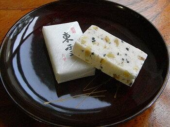 また、一般の落雁が最初に砂糖の甘みが先に伝わるのに対し、この二つの伝統菓子は、先に胡麻やクルミの香ばしさや風味が立ち上がります。噛んでいるうちに、段々と米特有の甘み、旨味が、じんわりと広がってくるのも共に同じの特徴となっています。  【菓子司 丸中の『東雲』は、終戦後の菓子の材料に不自由していた時期に、落雁を作った余りの材料に、近所の胡桃と胡麻を加えて誕生した菓子。名の由来は、『明けがらす』と同様に、明け方の空を意味し、胡桃は浮雲、胡麻は飛び交う小鳥たちの姿を表している。】