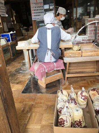 八戸の中心街から車で1時間程の距離にある三戸は、岩手県との県境にある内陸の町です。三戸には、昔ながらに鋳型を用いて、手焼きしているせんべい店が数々残っています。【手作業で煎餅を焼いている「小山田せんべい店」作業場】