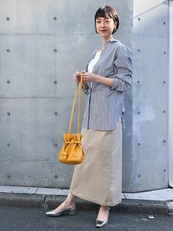 実はこのスカート、撥水加工が施されています。雨の日も気兼ねなくベージュのスカートが履けますよ♪シンプルなコーデはバッグで差し色を投入。