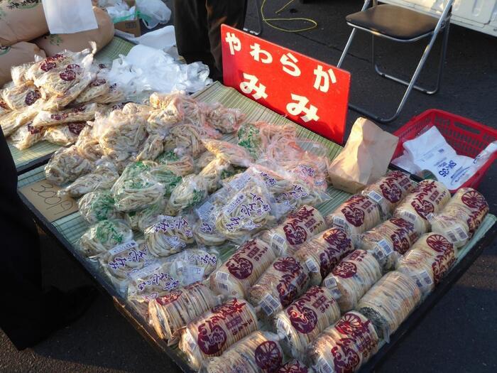 """町中の小さな作業場では、地元ならではの、餅せんべいと呼ばれる""""てんぽ""""や、汁物や鍋料理の具材となる""""白焼き""""と併せて、落花生、黒胡麻入りの伝統の「三戸せんべい」が一つ一つ手作業で焼かれています。出来たての煎餅は、店先の他、地元スーパーや市場などで販売されています。  【""""日本最大級のカオス朝市""""の「*館鼻岸壁朝市(たてはながんぺきあさいち)」の露店に並ぶ「小山田せんべい店」の『三戸せんべい』と『みみ』。""""みみ""""は、丸く仕上げる際に金型からはみ出た部分を切り落とした部分。厚みがあり、不揃いなので食感が良く、煎餅よりも好む人が多い。出来たては、柔らかく、時間の経過とともに硬くなるので、柔らかな""""みみ""""は、地元でしか味わえない。 (*館鼻岸壁朝市は、毎週日曜日の早朝にだけ出現する巨大朝市。JR八戸線陸奥湊駅から徒歩10分程度で着く岸壁で開催。)】"""