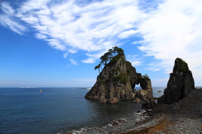 琥珀で有名な岩手県久慈市。北三陸に位置し、山間部から沿岸まで広がる市内には、「平沼高原」や「久慈渓流」等など、自然豊かな景勝地や観光スポットが点在しています。  【画像は、北部陸中海岸を代表する景勝地「久慈海岸」の『つりがね洞』。日本最古の地層からなる断崖と岩礁が続く海岸で、大小の小島が浮かぶ。『つりがね洞』は、その一つ島で、大きな洞穴の内部には釣鐘の形をした岩がぶら下がっていたことからその名が付いている。(内部の岩は、明治期の大津波で破壊され現存していない)】