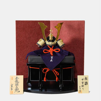 """鎌倉時代から江戸時代以降には、「菖蒲」が武を重んじる「尚武(しょうぶ)」と同じ読みであること、また菖蒲の葉の形が剣を連想させることから『菖蒲の節句』とも呼ばれ、武士の立身出世を願った風習になり、やがて、現在は鎧兜が""""身体を守る""""ものという意味が重視され、兜を飾って男の子の逞しい成長を願う行事として、広く浸透し、現代にも受け継がれています。"""
