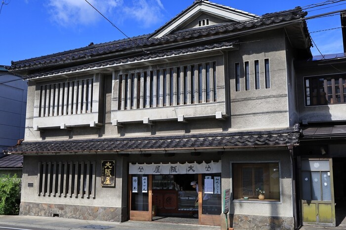 弘前城・追手門から徒歩5分程に店を構える「御菓子司 大阪屋」は、江戸初期の寛永7(1630)年創業。初代が弘前藩の御用菓子司なって以来、400年近くもの長きにわたってその味を受け継いできた、東北でも指折りの老舗です。  長子口伝されてきた製法と、昔ながらの手仕事を大切にしているため、「大阪屋」は、代々暖簾分けせず一店主義。地元の食材を用い、伝統製法による菓子は、どれも無添加で傷みやすいため、支店を設けず、卸売もしてません。  【黒字に金色の店名の看板、暖簾が掛かる風格ある店構え。店内には、緻密な螺鈿細工の菓子箪笥が置かれ、藩に仕えた名残が今も色濃く残っている。】
