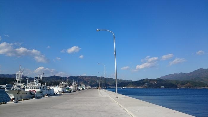 「山田町」は、先の東日本大震災で、壊滅的な被害を受けた町。大津波と火災の発生によって、町の中心部は、瓦礫が折り重なり、焼け野原と化しましたが、地元の方々の奮励努力によって復興が進み、現在では沿岸部も町も整備されています。  【山田湾船着き場。「山田湾」も三陸復興国立公園の景勝地の一つ。「オランダ島」などの小島、牡蠣や帆立の養殖筏が浮かぶ景観が有名。(画像は、震災3年後の2014年撮影のもので、海上に養殖筏がないが、現在は養殖筏も復活している。】
