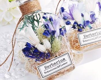 """ガラス瓶の中に、専用のオイルでお花を浸して作られるハーバリウム 。作家さんによって異なる世界観が作り出されているので、お気に入りを探している時間も楽しいですよね*こちらは""""初夏の庭""""と名付けられている通り、爽やかなデザインが素敵な作品です。"""