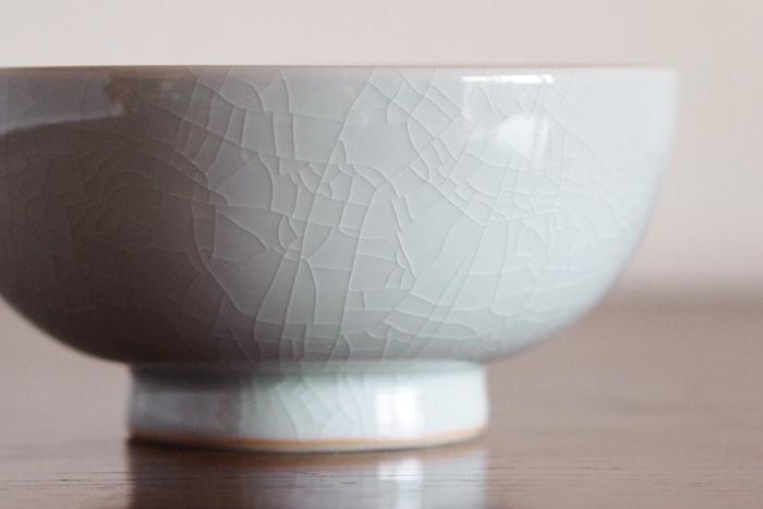 古染土と呼ばれる陶土を用いて作られており、釉薬のひび割れである貫入が見えやすいよう、透明釉が施されているので、ほんのりと青みを帯びた白色に、まるで美しい模様のように、ひび割れが浮び、シンプルな白色の茶碗がとても味わい深い仕上がりになっています。