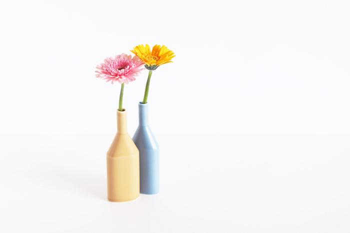 手の平サイズのスリムな一輪挿し。すべすべの質感と柔らかな色合いに心癒されます。季節の花をさりげなく挿すだけで、陽の光を感じるような暖かさがある器です。