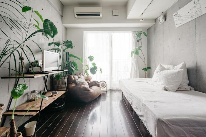 縦長のお部屋にベッドに対面してテレビが置かれたレイアウトです。コンクリート打ちっ放しの無機質なお部屋の中でも、一目置かれるテレビ台はセミオーダーして作ったもの。テレビはベッドからゆったりくつろぎながら見ることができるベストポジションの位置に。シンプルなお部屋にたくさんのグリーンを飾ることでぐっと華やいだ印象になります。