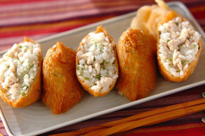 酢飯に鶏そぼろと刻んだ三つ葉を混ぜれば、いつものいなり寿司がちょっと新鮮な味に変わります。きれいにカットして中身を見せる盛り付け方もいいですね♪