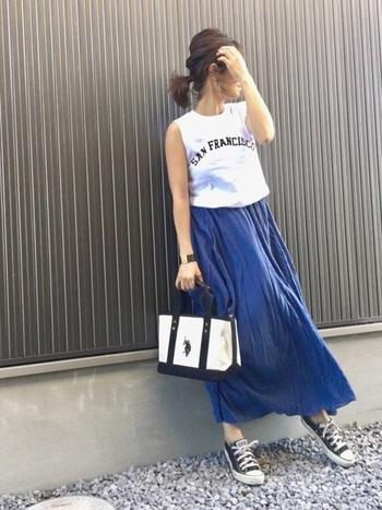 凹凸のある生地をたっぷりと使ったボリュームスカートですが、エアリーな軽やかさもあって深みのあるブルーが甘すぎない大人という印象で、とても素敵ですね。ボトムスに重さがあるので、トップスはノースリーブですっきりと。縦長のラインに目が行って、すらりとした印象を作り出せます。