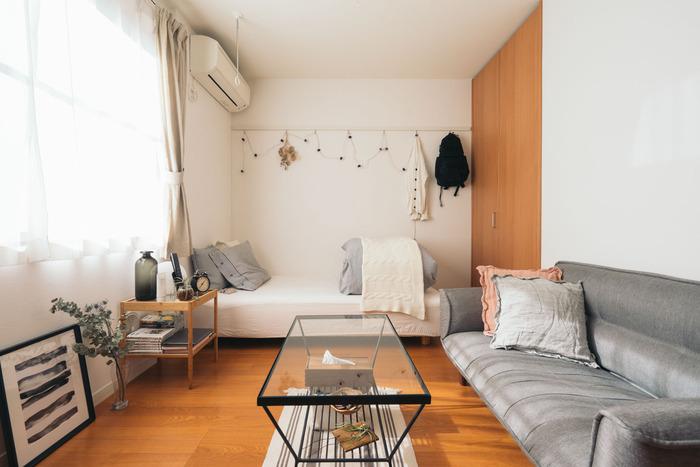 奥の壁にベッドを配置し、左右一方の壁にソファを配置するL字レイアウト。スペースが限られている一人暮らしさんのお部屋の定番スタイルです。ベッドカバーと奥の壁の色を合わせることで、広々とした印象になるようまとめています。