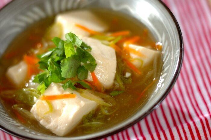 身体がぽかぽかと温まる絹ごし豆腐のあんかけレシピ。味付けを控えめにしてだし汁の風味を生かすことで、優しい味わいに。 隠し味に加えたしょうがの香りがアクセント。ニンジンのオレンジとミツバの緑のコントラストが上品な一品です。