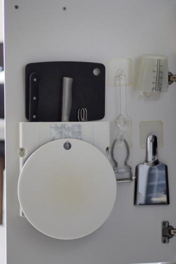 他のキッチンツールと一緒に、シンク下の扉の下に吊り下げて収納するアイデア。取っ手が付いているプラスチック製の計量カップの収納におすすめの方法です。大さじや小さじなど、一緒に使うものが近くにあると、より便利に◎